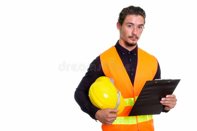 Studio shot of young handsome man construction worker holding ha royalty free stock photography