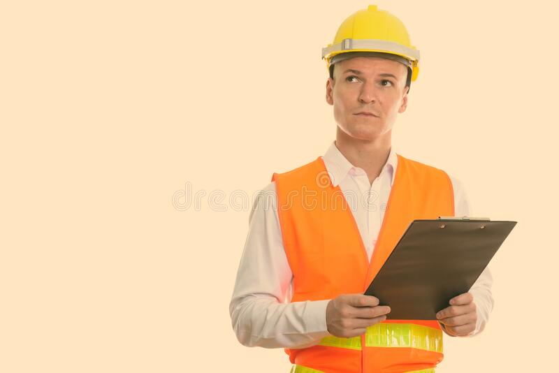 Studio shot of young handsome man construction worker holding clipboard while thinking royalty free stock images