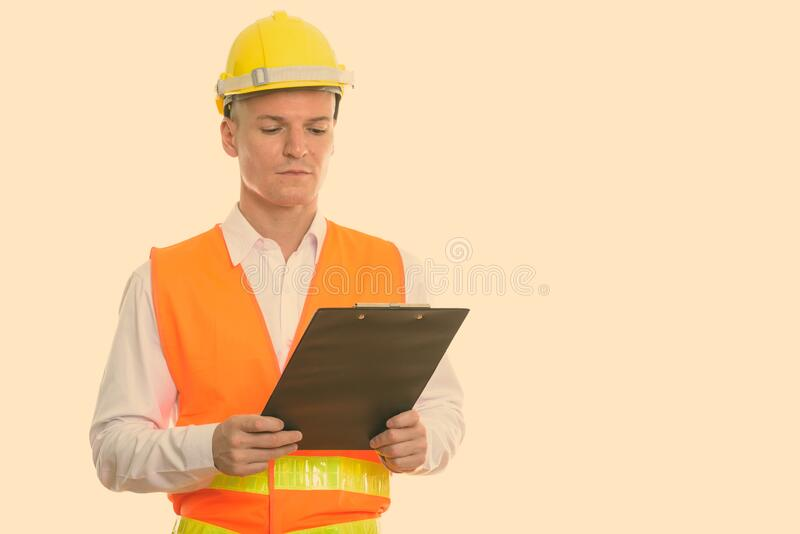 Studio shot of young handsome man construction worker reading on clipboard royalty free stock image
