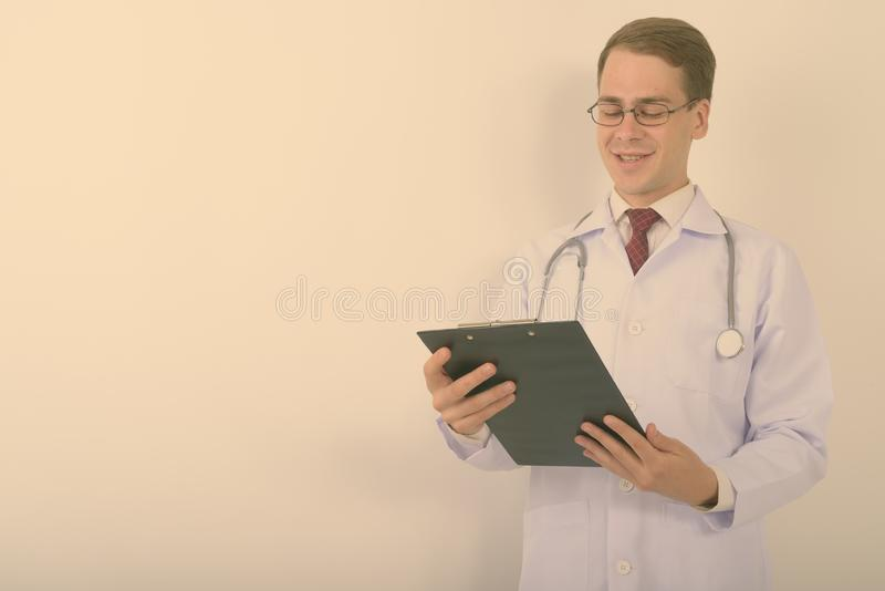 Young handsome man doctor wearing eyeglasses against white background stock photography