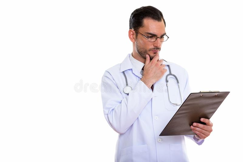 Studio shot of young handsome man doctor thinking while looking. At clipboard stock photos