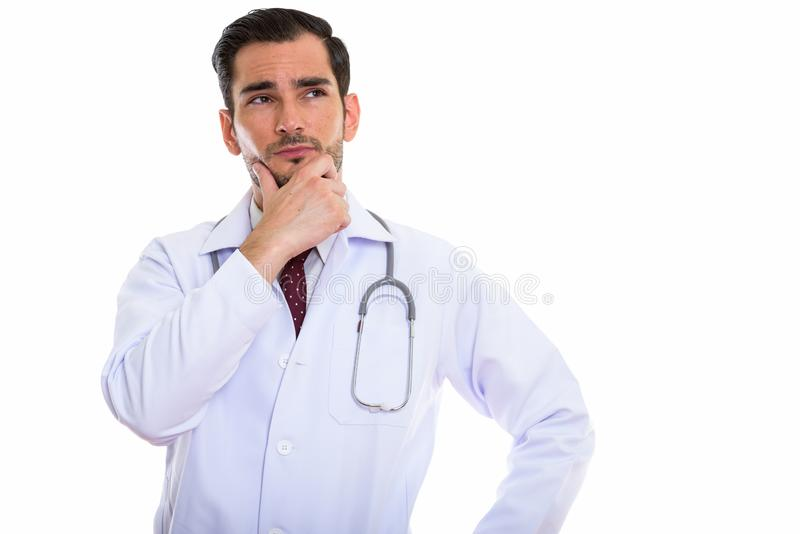 Studio shot of young handsome man doctor thinking while looking. Up royalty free stock photos