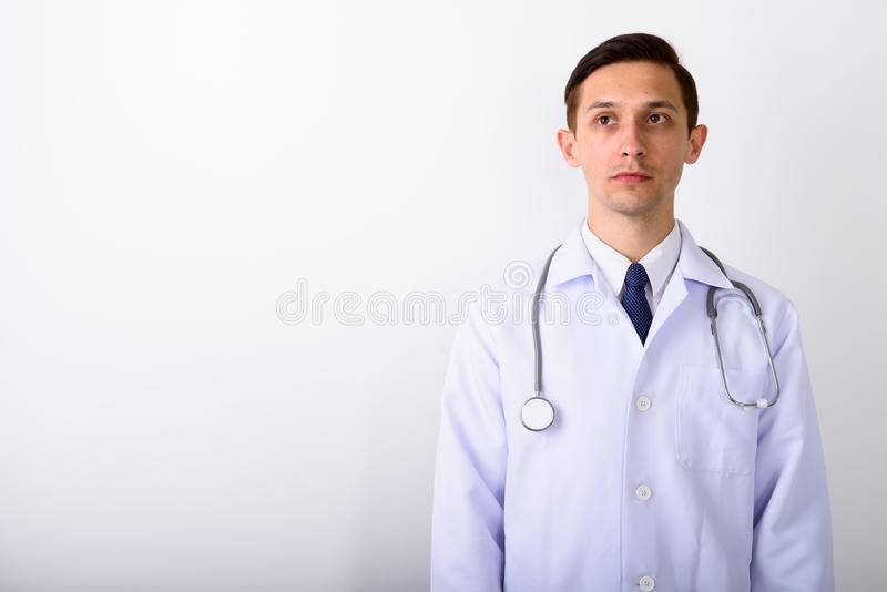 Studio shot of young handsome man doctor thinking while looking. Up against white background stock photo