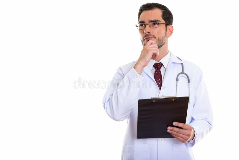 Studio shot of young handsome man doctor thinking while looking. Up and holding clipboard stock image