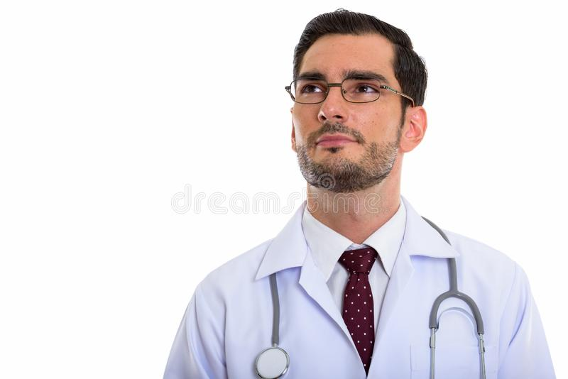 Studio shot of young handsome man doctor thinking while looking. Up and wearing eyeglasses stock image