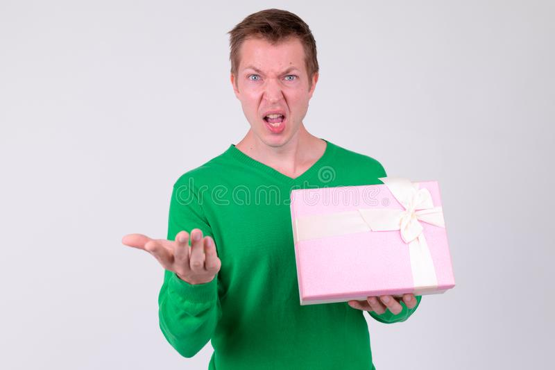 Annoyed young man with gift box ready for Valentine`s day. Studio shot of young handsome man ready for Valentine`s day against white background royalty free stock photo