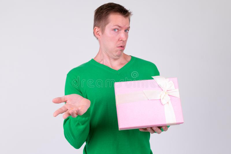 Young man shrugging shoulders with gift box ready for Valentine`s day. Studio shot of young handsome man ready for Valentine`s day against white background stock image