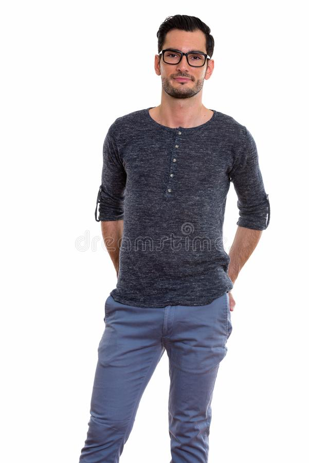 Studio shot of young handsome man standing with hands on back po stock photos