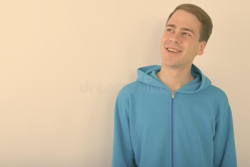 Young handsome man wearing blue hoodie against white background stock images
