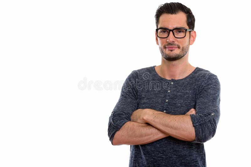 Studio shot of young handsome man wearing eyeglasses with arms c royalty free stock photography