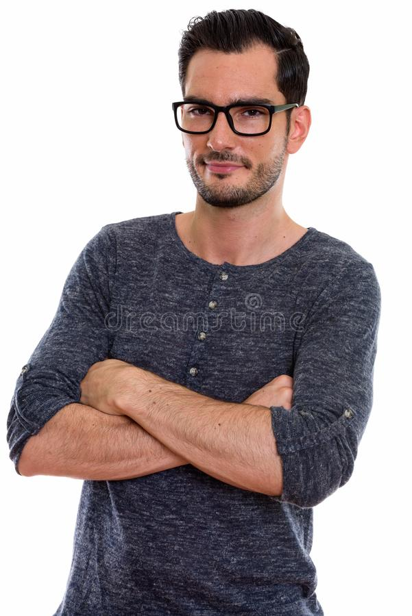 Studio shot of young handsome man wearing eyeglasses with arms c royalty free stock photo