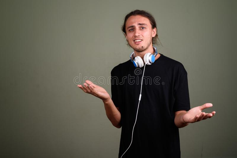 Young handsome man wearing headphones against colored background. Studio shot of young handsome man wearing headphones against colored background stock image