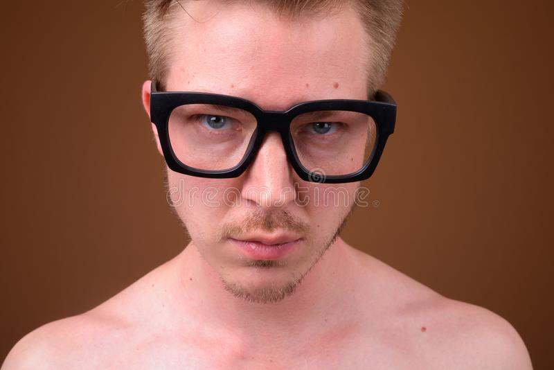 Face of young nerd man wearing big eyeglasses. Studio shot of young handsome nerd man shirtless against brown background stock images