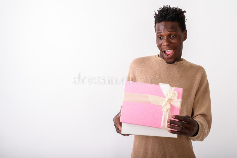Studio shot of young happy black African man smiling while openi. Ng gift box and looking shocked against white background royalty free stock photos