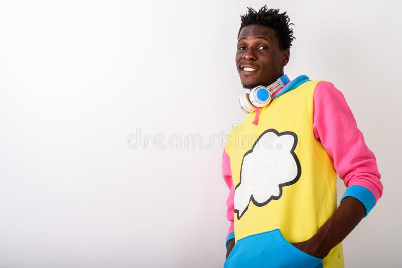 Studio shot of young happy black African man smiling while posin. G with hands on front pockets and wearing headphones around neck against white background stock images