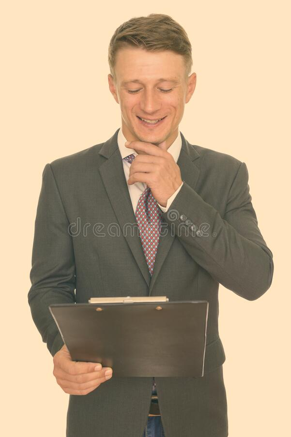 Studio shot of young happy Caucasian businessman reading clipboard and thinking stock images