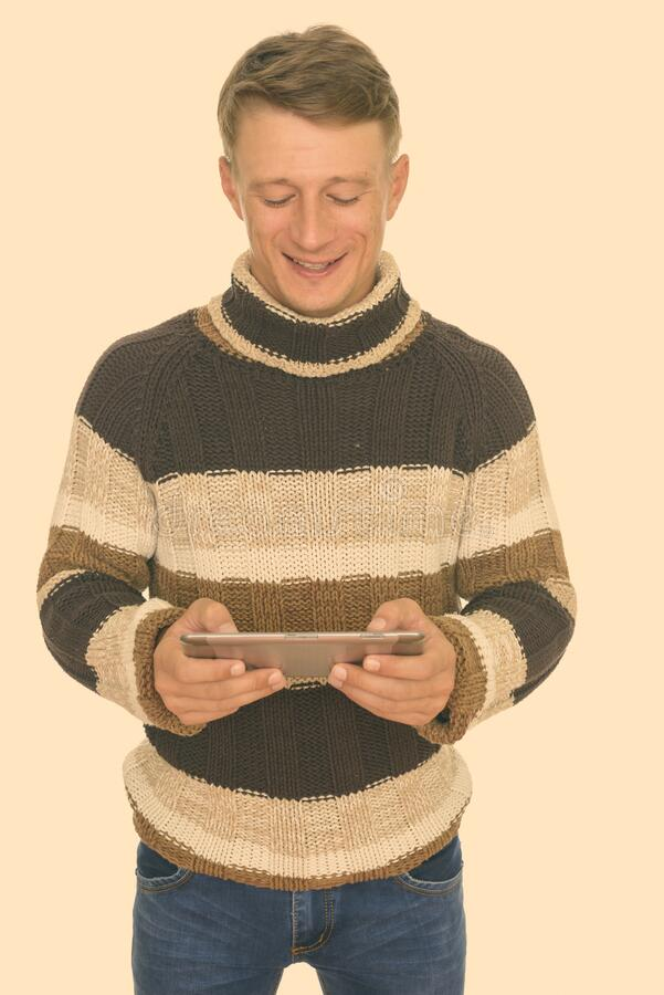 Studio shot of young happy Caucasian man using digital tablet isolated against white background stock image