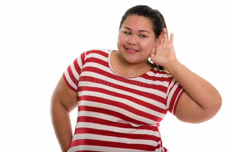 Studio shot of young happy fat Asian woman smiling and listening. Isolated against white background royalty free stock images
