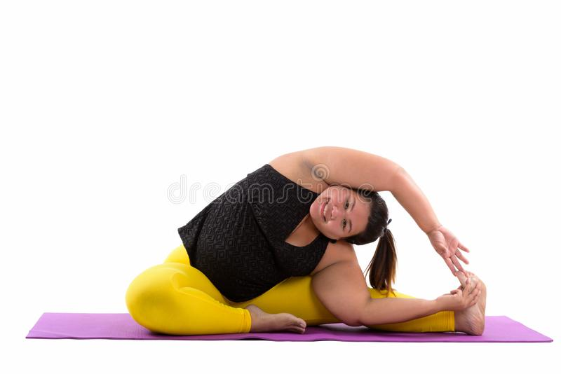 Studio shot of young happy fat Asian woman smiling and reaching stock photo