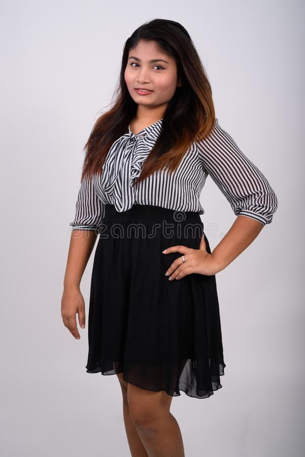 Studio shot of young happy fat Persian businesswoman smiling whi stock photography
