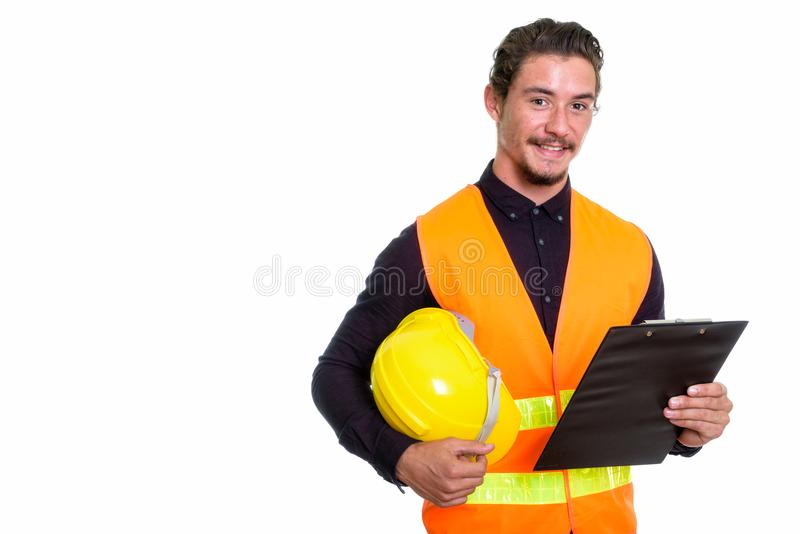 Studio shot of young happy man construction worker smiling while stock photo