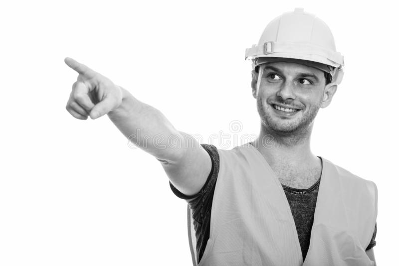 Studio shot of young happy man construction worker smiling while pointing finger. Studio shot of young man construction worker isolated against white background royalty free stock photos