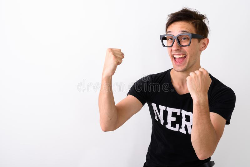 Studio shot of young happy nerd man smiling while thinking and l. Ooking excited against white background stock images