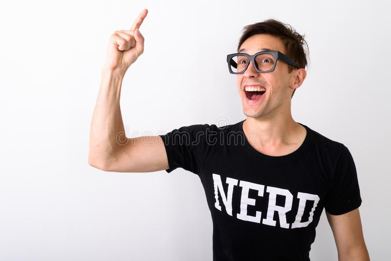 Studio shot of young happy nerd man smiling while thinking and p. Ointing finger up against white background royalty free stock image