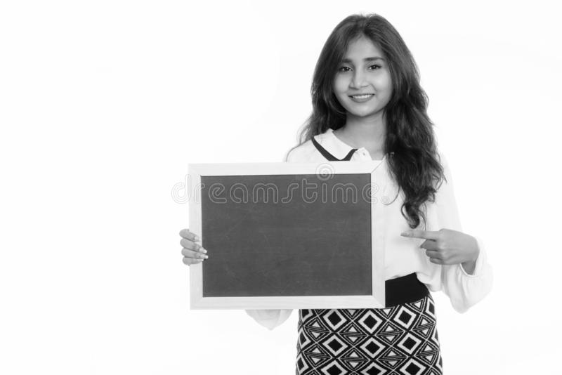 Studio shot of young happy Persian businesswoman smiling while holding and pointing at blank blackboard royalty free stock image