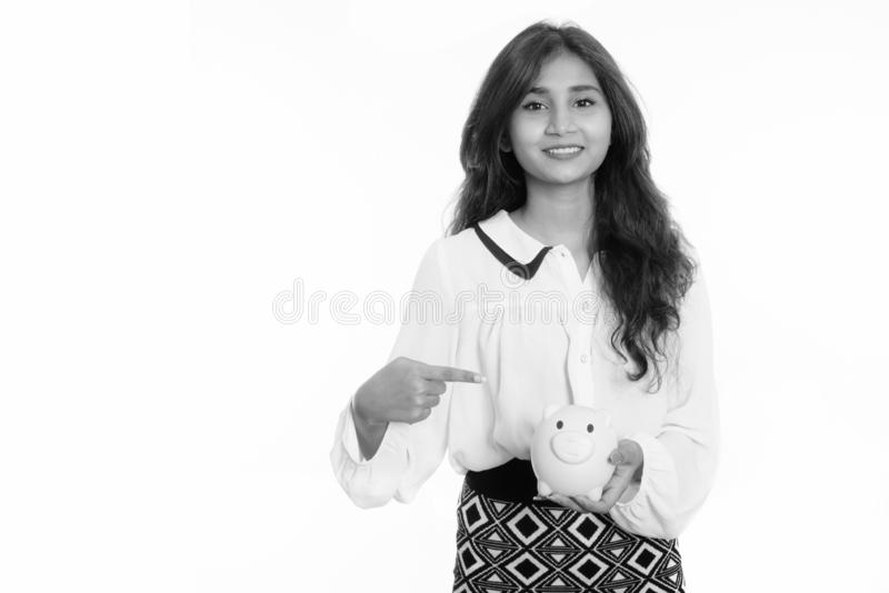 Studio shot of young happy Persian businesswoman smiling while holding and pointing at piggy bank royalty free stock photos
