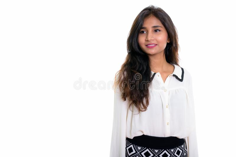 Studio shot of young happy Persian businesswoman smiling while t royalty free stock photo