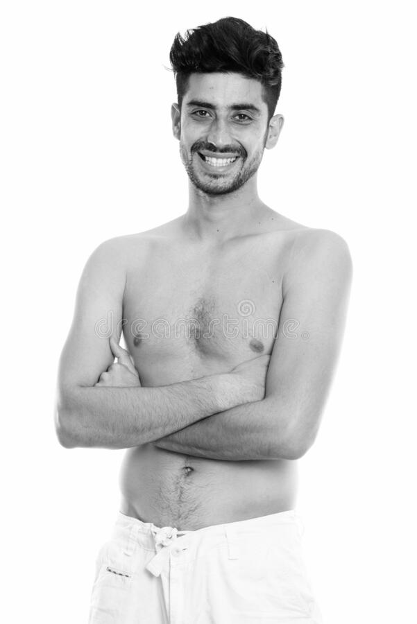 Studio shot of young happy Persian man smiling while standing shirtless with arms crossed stock image