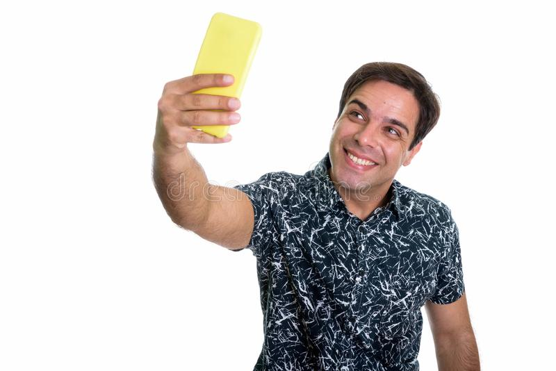 Studio shot of young happy Persian man smiling while taking self. Ie picture with mobile phone isolated against white background royalty free stock photography