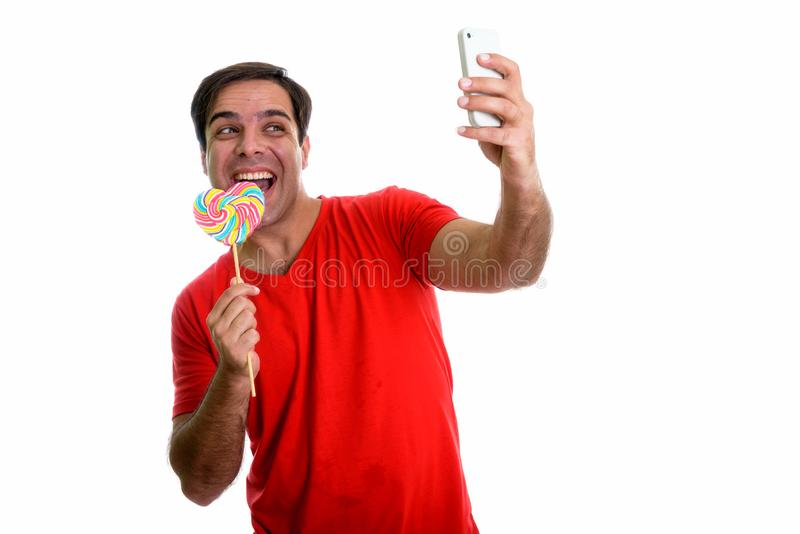 Studio shot of young happy Persian man smiling and taking selfie. Picture with mobile phone while eating heart shaped lollipop isolated against white background royalty free stock image