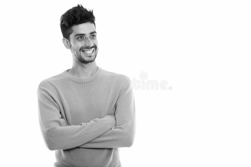 Studio shot of young happy Persian man smiling and thinking with arms crossed stock images