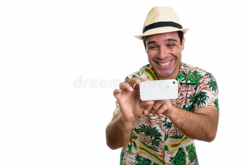 Studio shot of young happy Persian tourist man smiling while tak. Ing picture with mobile phone isolated against white background royalty free stock images