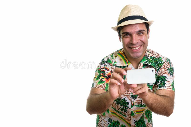 Studio shot of young happy Persian tourist man smiling while tak. Ing picture with mobile phone and looking at camera isolated against white background royalty free stock photos