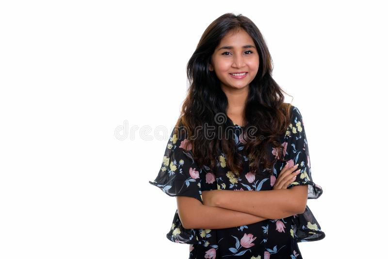Studio shot of young happy Persian woman smiling with arms cross royalty free stock images