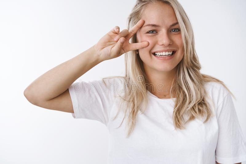 Studio shot of young healthy attractive caucasian woman blond hair smiling friendly and carefree, showing peace victory stock photography