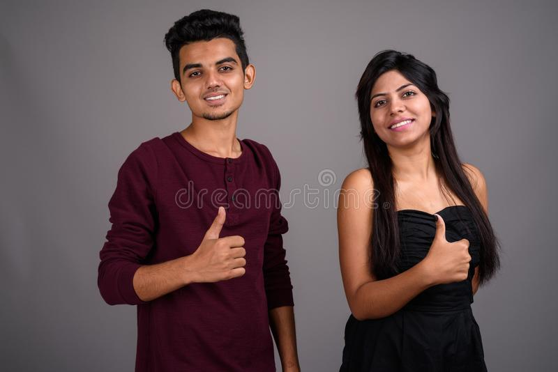 Young Indian man and young Indian woman together against gray ba stock photos