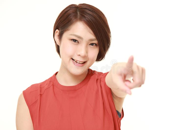 Studio shot of Japanese woman decided on white background. Studio shot of young Japanese woman in red on white background stock photo