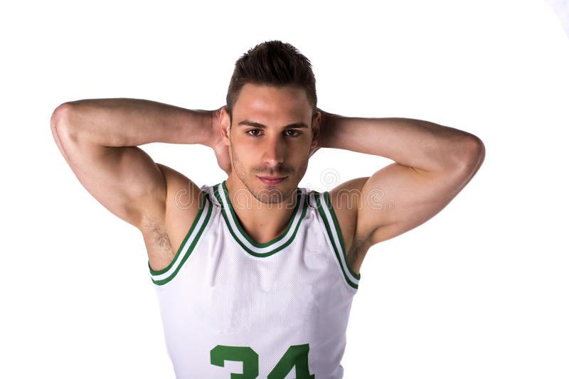 Studio shot of young man in basketball tank-top. Stading isolated on white background, rising hands behind his head royalty free stock photography