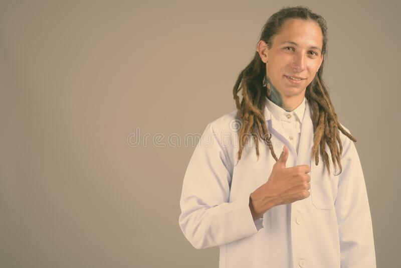 Young man doctor with dreadlocks against gray background royalty free stock images