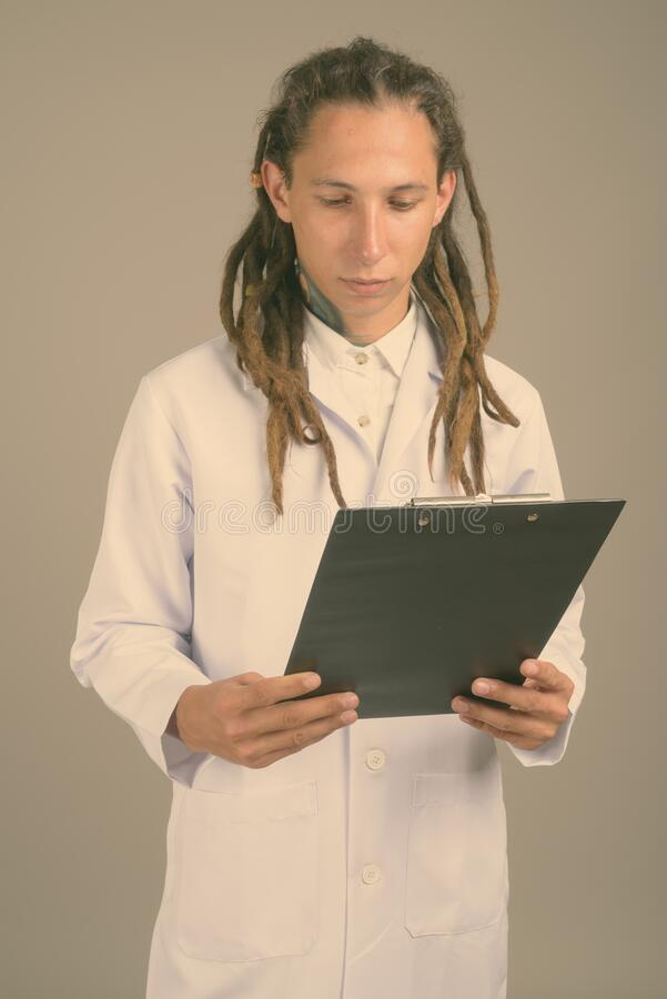Young man doctor with dreadlocks against gray background royalty free stock image