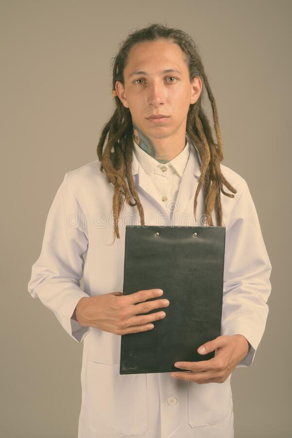 Young man doctor with dreadlocks against gray background royalty free stock photography