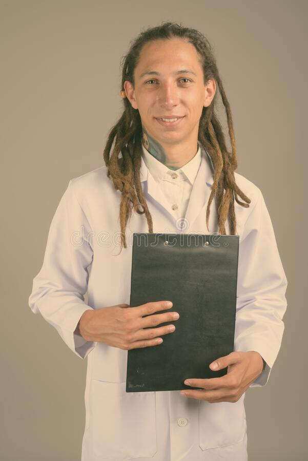 Young man doctor with dreadlocks against gray background royalty free stock photos