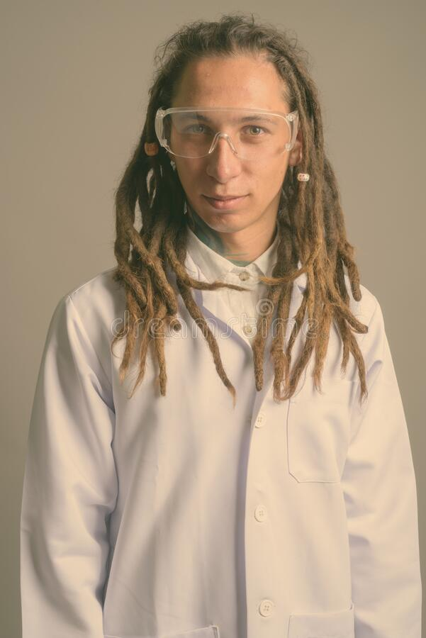 Young man doctor with dreadlocks wearing protective glasses against gray background royalty free stock photos
