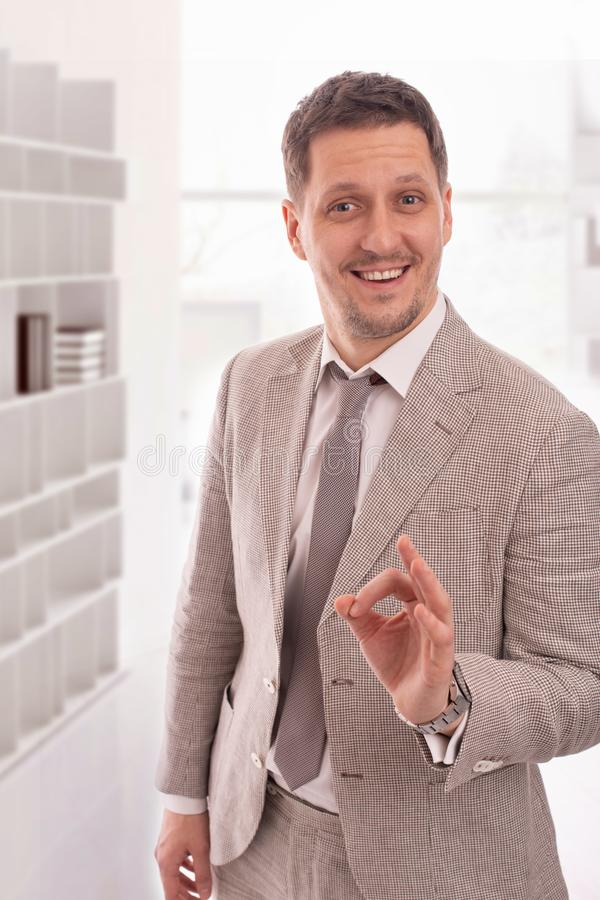 Studio shot of a young man wearing beige suit giving you an approving gesture against a whait background royalty free stock photo