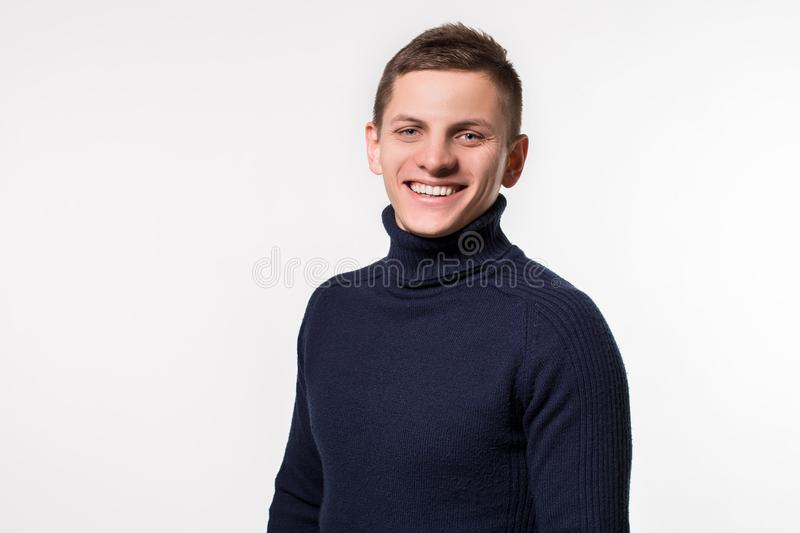 Studio shot of young man wearing blue turtleneck sweater against stock photo
