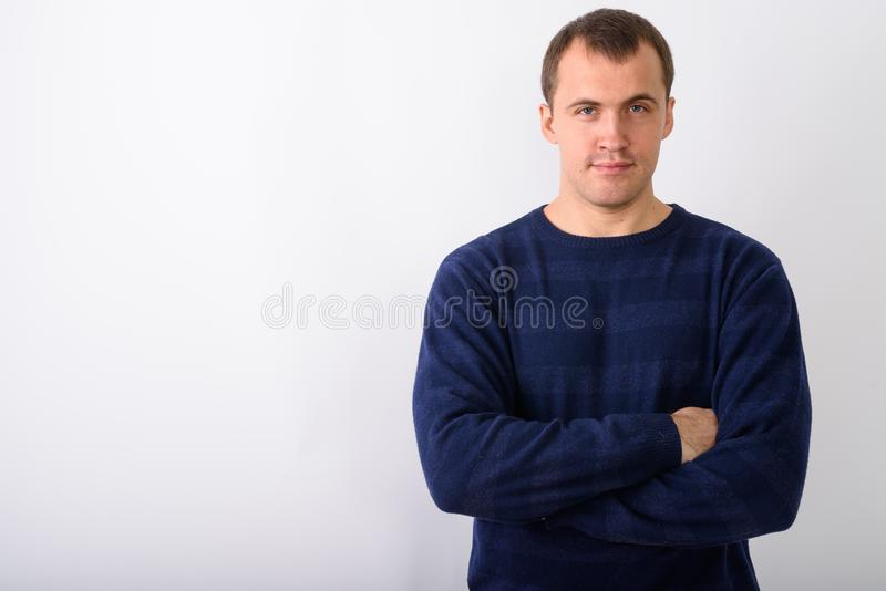 Studio shot of young muscular man with arms crossed against whit royalty free stock photos